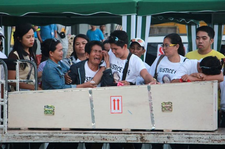 The mother of murdered Filipina maid Joanna Demafelis crying in front of the casket containing her body, after it arrived at Iloilo International Airport on Feb 17, 2018.