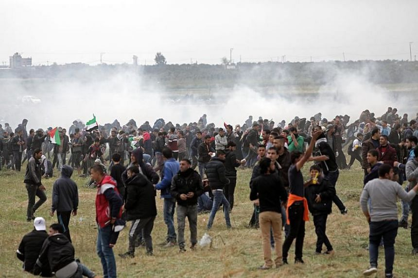 Palestinian protesters running away after Israeli soldiers fired tear gas at them, during a demonstration along the border between Israel and the Gaza Strip, on March 30, 2018.