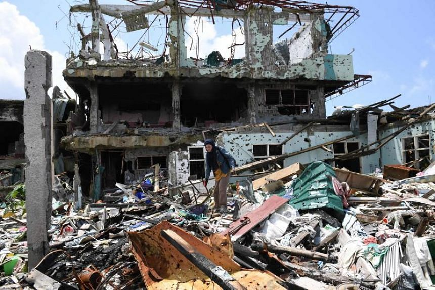 A resident stands among the rubble of her home while salvaging her belongings, in Marawi city on April 1, 2018.