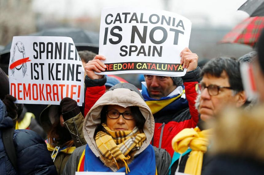 Protesters hold posters during a demonstration organised by the Catalan pro-independence association ANC in Berlin on April 1, 2018.