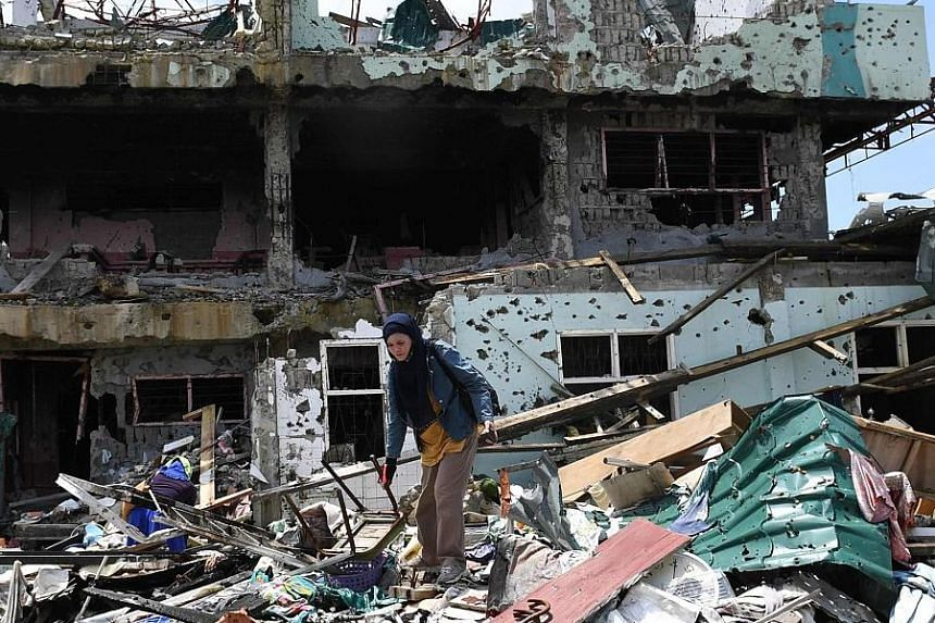 A woman trying to salvage some belongings from her destroyed house in Marawi city yesterday.