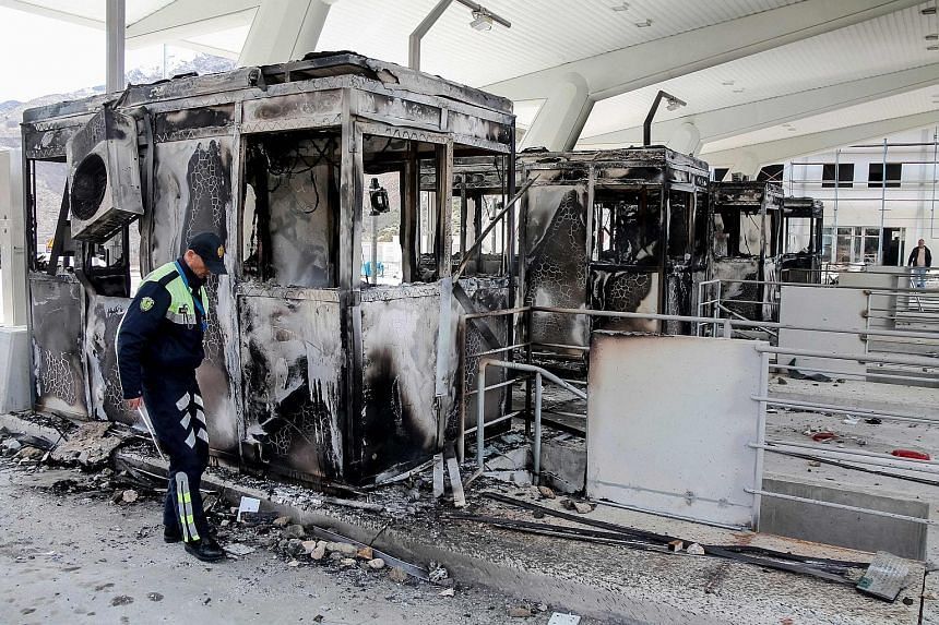 An Albanian police officer inspecting charred toll booths at the Durres-Kukes highway, which links Albania and Kosovo, last Saturday. The booths at the Morina border crossing were set alight by protesters after a decision to introduce a toll on the h