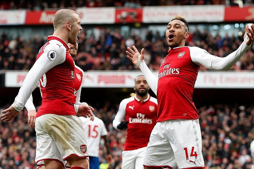Arsenal's Pierre-Emerick Aubameyang celebrating breaking the deadlock against Stoke from the spot with team-mate Jack Wilshere. The Gabonese striker scored another from a corner before passing up the opportunity for a hat-trick, instead allowing stri
