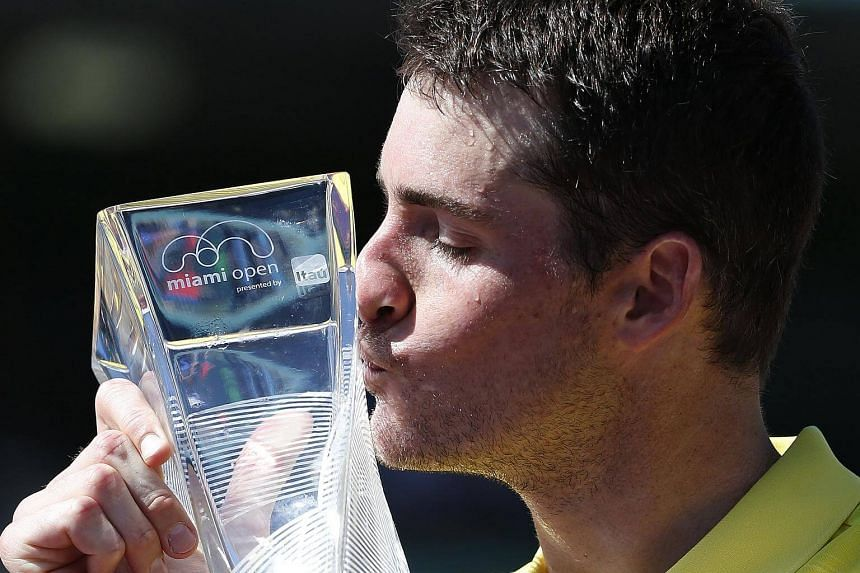 John Isner of the US kisses his trophy after defeating Alexander Zverev of Germany during their finals match at the Miami Open tennis tournament on Key Biscayne, Miami, Florida, US, on April 1, 2018.