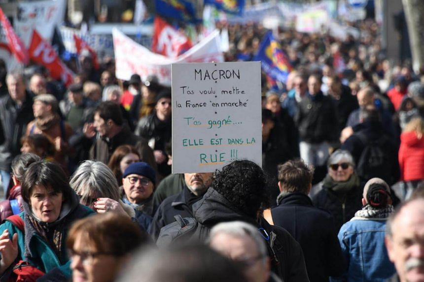 People take part in a demonstration to protest against the French government's string of reforms in Toulouse on March 22, 2018.