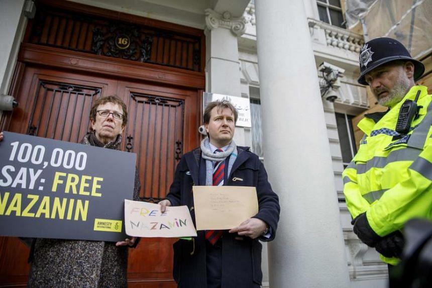 Richard Ratcliffe (right), husband of jailed British-Iranian woman Nazanin Zaghari-Ratcliffe, delivers a petition and a letter addressed to the Iranian Deputy Foreign Minister Abbas Araghchi to demand her release, at the Iranian Embassy in London on