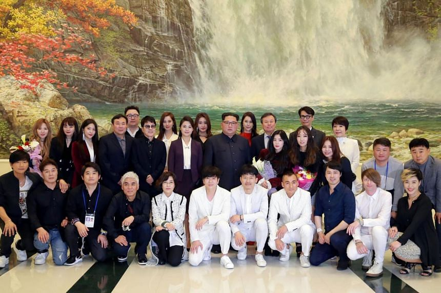 North Korean leader Kim Jong Un (back row, centre) and his wife Ri Sol Ju (back row, sixth from left) posing with South Korea's Culture, Sports and Tourism Minister Do Jong Hwan (back row, eighth from right) and South Korean musicians after a concert