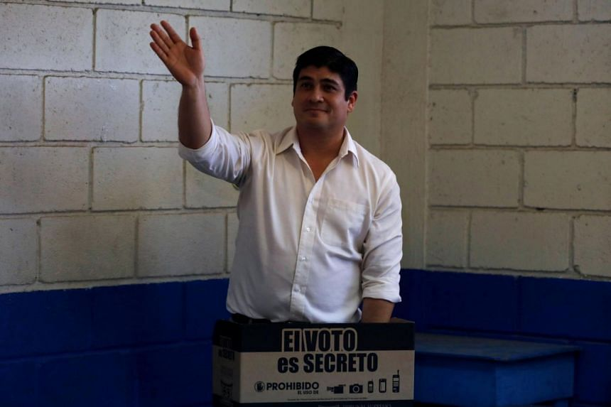 Carlos Alvarado Quesada holding up his ballot during the presidential election at a polling station in San Jose, Costa Rica, on April 1, 2018.