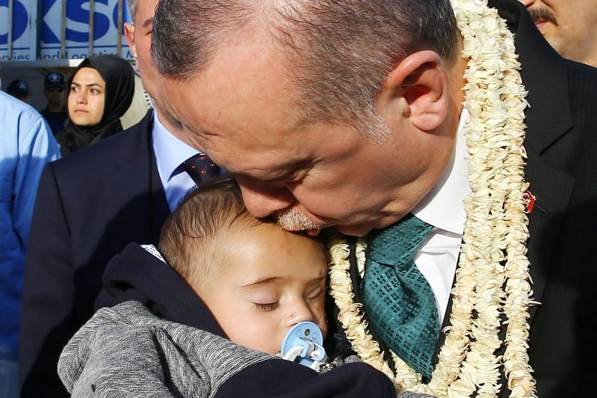 Turkish President Recep Tayyip Erdogan kisses Syrian infant Karim Abdallah during his visit to border units in Turkey's Hatay province on April 1, 2018.