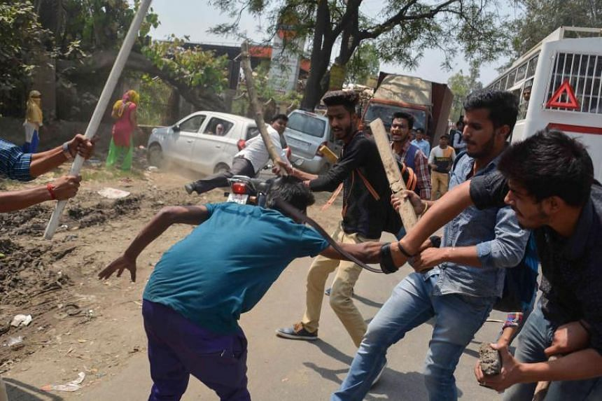 """A protester is beaten by Indian students after members of the Dalit community and other """"low-caste"""" groups threw bricks at their college, during countrywide protests in Meerut in Uttar Pradesh state on April 2, 2018."""