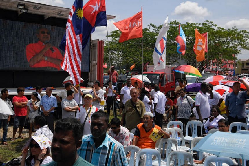 Pakatan Harapan chairman Mahathir Mohamad is seen on a screen as the crowd listens during a rally in Ayer Hitam in Malaysia's Johor state on March 18, 2018.