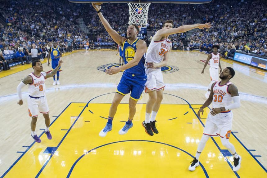 Golden State Warriors guard Klay Thompson shoots the basketball against Phoenix Suns forward Dragan Bender during the first half of hte game at Oracle Arena on April 1, 2018.