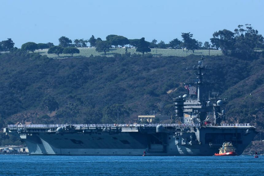 The USS Theodore Roosevelt sails past Fort Rosecrans National Cemetery as it leaves port on deployment to the western Pacific Ocean and Persian Gulf from San Diego, on Oct 6, 2017.
