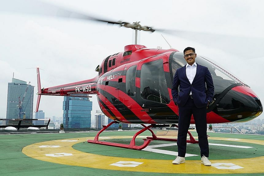 Above: A Bell 505 Jet Ranger helicopter flying over Jakarta. Left: Whitesky Aviation CEO Denon Prawiraatmadja on the helipad of Shangri-La hotel in Jakarta, currently one of the locations where customers can board or be dropped off.
