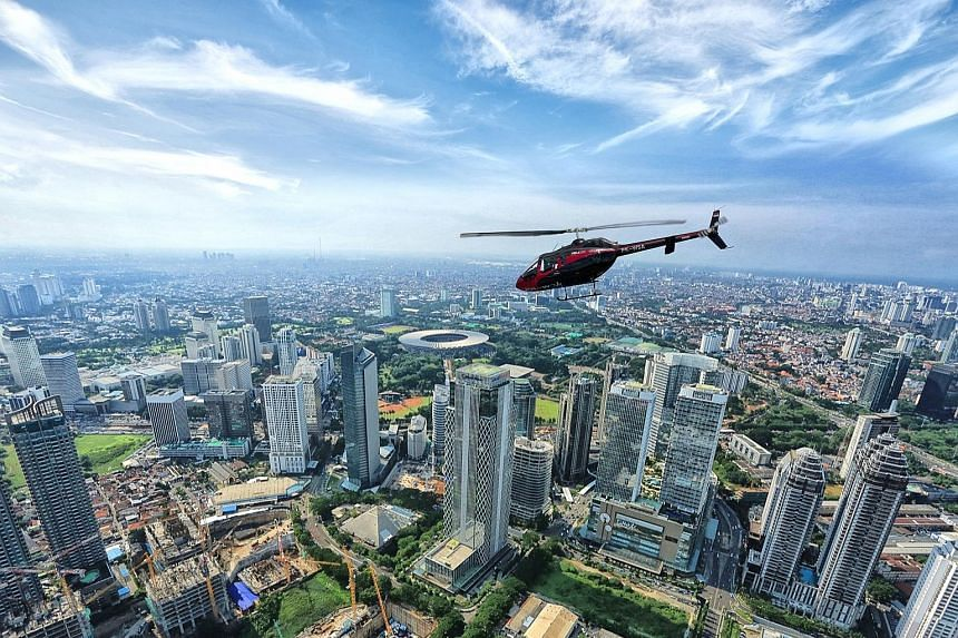 Left: Beating a traffic jam in Jakarta high above in a Helicity helicopter. Above: Arriving in style on the rooftop helipad at Shangri-La hotel. Below: Whitesky Aviation launched helicopter-taxi service Helicity which allows customers to book rides f
