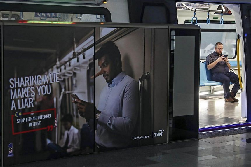 An advertisement warning members of the public not to spread fake news is seen in Kuala Lumpur on March 31, 2018. Malaysian lawmakers approved an anti-fake news law on April 2, 2018.