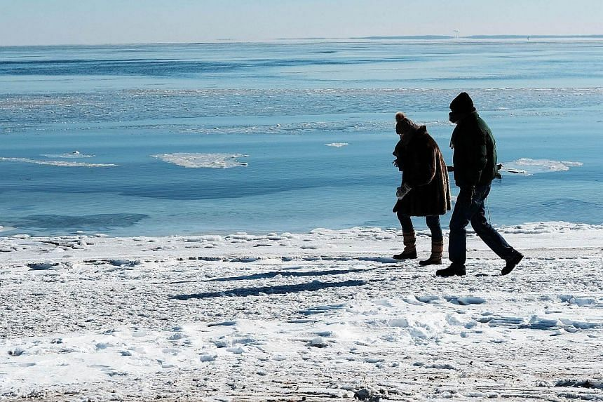 People walk along a beach covered in snow and ice as temperatures continue to stay below freezing in much of the north-east, on Jan 7, 2018 in Westport, Connecticut.