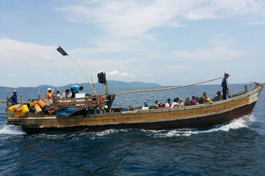 A wooden boat carrying Rohingya refugees being guided by Royal Thai Navy personnel (seen standing in dark outfit on the bow) as it sails towards Thailand-Malaysia sea boundary escorted by Thai Navy boat (not in picture), on April 1, 2018.