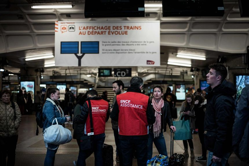 French National Railway Corporation employees assist travelers at the Lyon Part-Dieu railway station, on the first evening of a two-day strike, on April 2, 2018 in Lyon.
