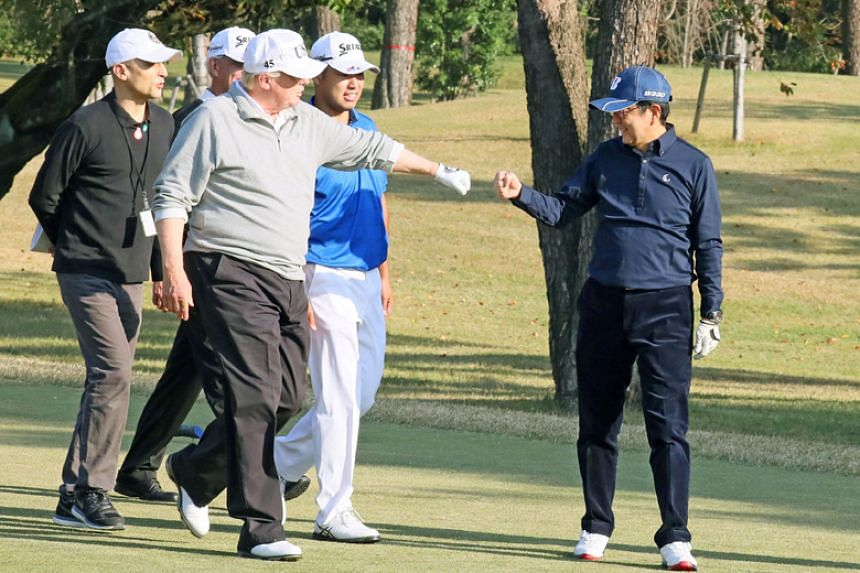 """US President Donald Trump """"fist bumps"""" Japan's Prime Minister Shinzo Abe as they play golf at the Kasumigaseki Country Club in Kawagoe, Japan, on Nov 5, 2017."""