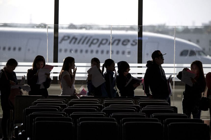 Filipina workers returning home from Kuwait arrive at Manila's Ninoy Aquino International Airport on Feb 18, 2018.