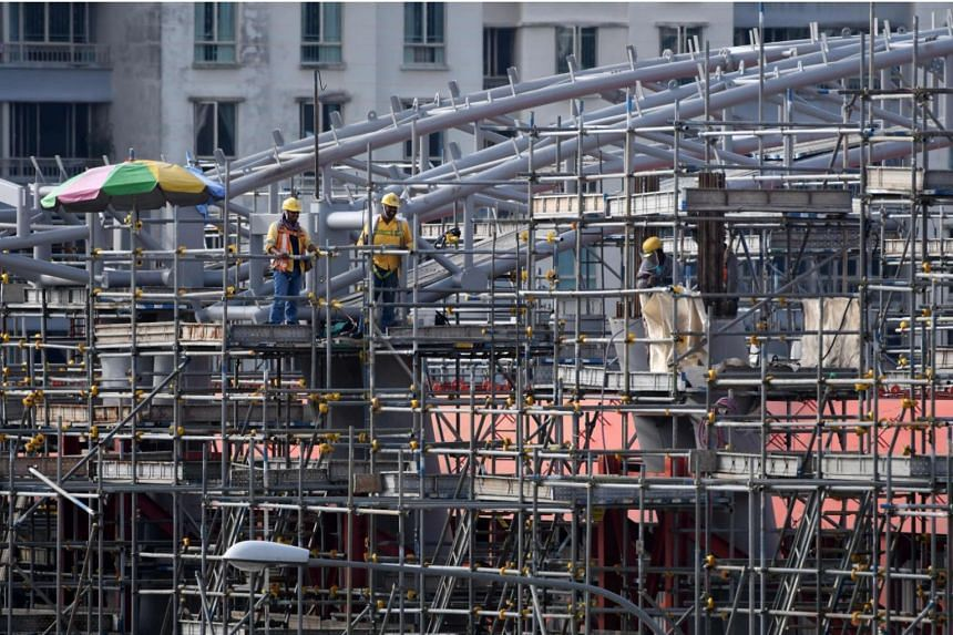 File photo showing workers standing on scaffolding at a construction site in Singapore on March 5, 2018.