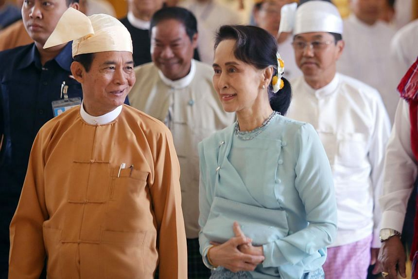 Myanmar's President Win Myint (left) and State Counsellor Aung San Suu Kyi (right) arrive at the parliament in Naypyidaw to take his oath of office, on March 30, 2018.