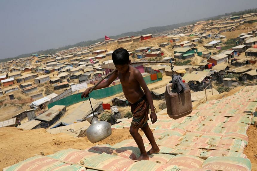 A Rohingya refugee boy carries water in the Kutupalong refugee camp, in Cox's Bazar, Bangladesh, on March 22, 2018.