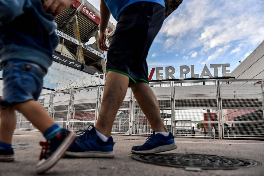 A child and a man walk past the entrance of Argentinian football club River Plate in Buenos Aires on April 2, 2018.