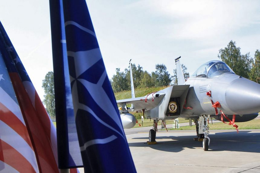 A US Air Force F-15C Eagle jet next to flags of the US and the Nato during an exercise of Nato's Baltic air-policing mission at the Siauliai Air Base in Siauliai, Lithuania.