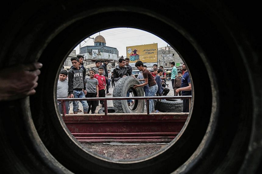 Palestinian protesters collecting tyres in Khan Yunis in the southern Gaza Strip yesterday as a tent protest raged on. Tens of thousands protested at the border with Israel last Friday, and violent clashes saw 18 Palestinians die and hundreds more in