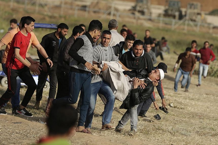 Palestinian demonstrators carrying a man shot by Israeli forces during clashes on Monday as they protested along the border with Israel, east of Gaza City, in support of Palestinian refugees' right of return to areas from which they fled or were expe