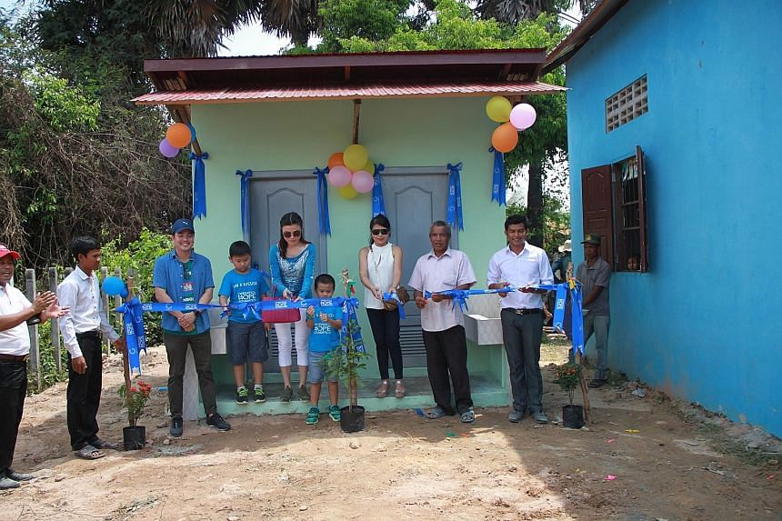 The new playground that donors from Holiday for Hope helped to fund at Ta Snae Primary School in Siem Reap. Ms Jilly Wang (in blue) with her sons Lim Wei Chen (left) and Lim Wei Kheng at a ceremony to mark the opening of new toilets at Ta Snae Primar