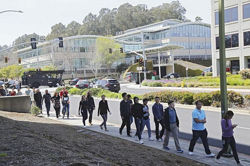 YouTube employees walk away from their place of work, in background, after a shooting incident, in San Bruno, California on April 3, 2018.