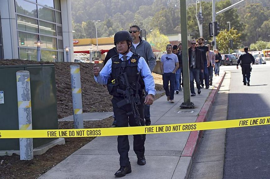 A police officer leads a group of YouTube employees down a sidewalk outside their place of work after a shooting incident, in San Bruno, California on April 3, 2018.
