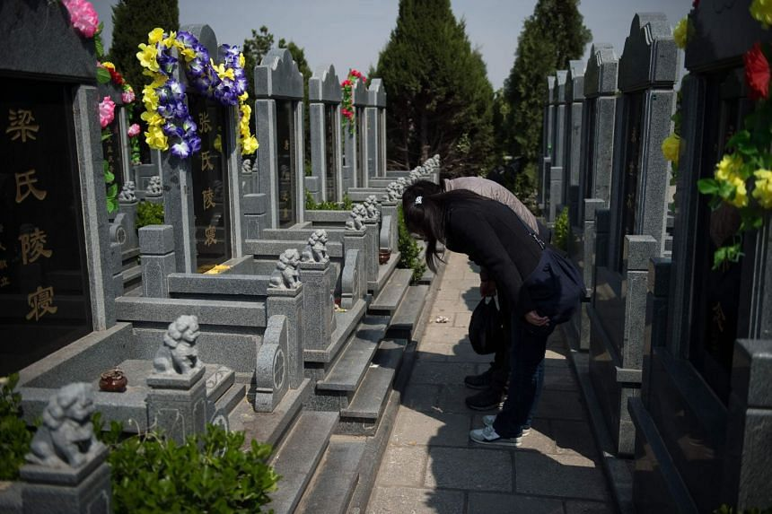 Family members bow at a grave ahead of the annual Qingming festival, or Tomb Sweeping Day, at a cemetery in Beijing, on April 2, 2017.
