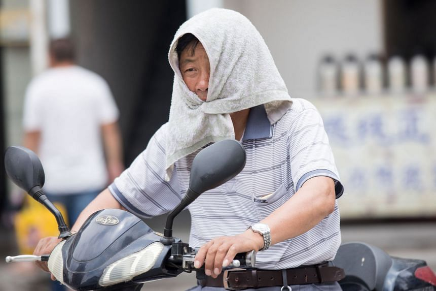 A man is seen with a towel tied around his head during a heat wave in Hangzhou, China on July 10, 2017.