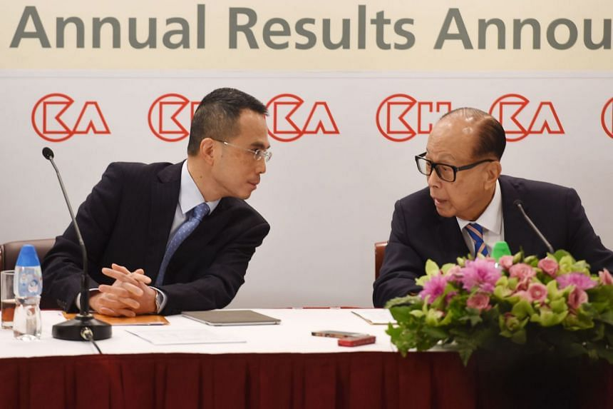 Hong Kong's richest man Li Ka-shing (right), 89, speaks to his son, Victor, during a press conference in Hong Kong on March 16, 2018.