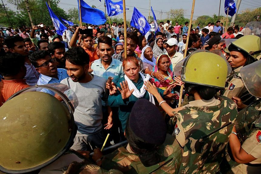 Police try to stop people belonging to the Dalit community as they take part in a protest during a nationwide strike called by Dalit organisations in India on April 2, 2018.
