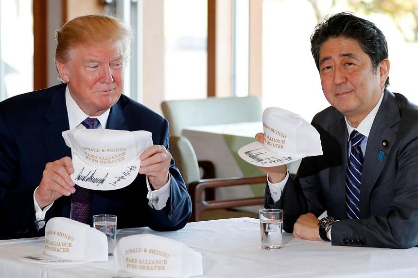 US President Donald Trump (left) and Japan's Prime Minister Shinzo Abe holding hats they signed for each other before a round of golf at the Kasumigaseki Country Club in Japan on Nov 5, 2017.