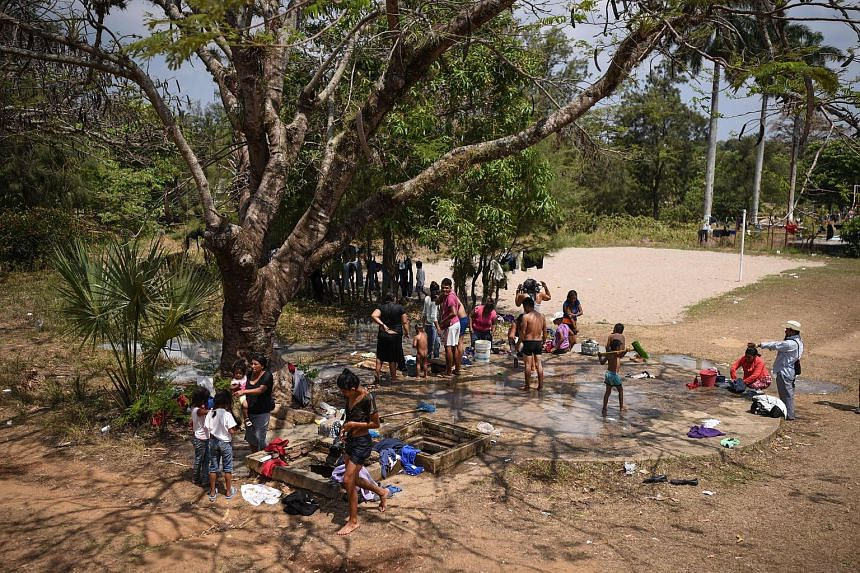 Central American migrants taking part in a caravan towards the United States having a bath at a sports field in Matias Romero, Oaxaca State, Mexico, on April 3, 2018.