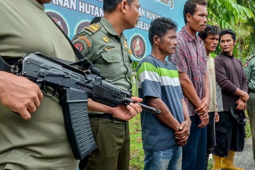 Indonesian rangers with the suspects, who have been charged. If convicted, they could face five years in prison and 100 million rupiah (S$9,500) in fines.
