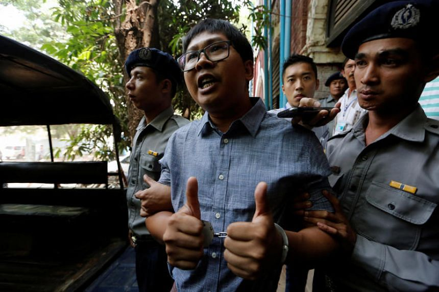 Detained Reuters journalist Wa Lone is escorted by police after a court hearing in Yangon, on April 4, 2018.
