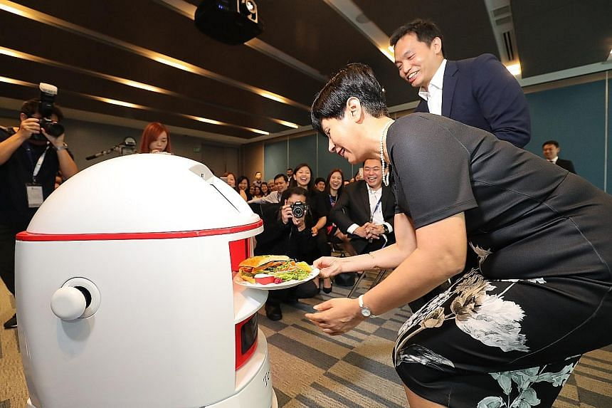 Senior Minister of State for Law and Finance Indranee Rajah getting a roast chicken sandwich, which she had ordered remotely using the mobile app, from Max the robot.