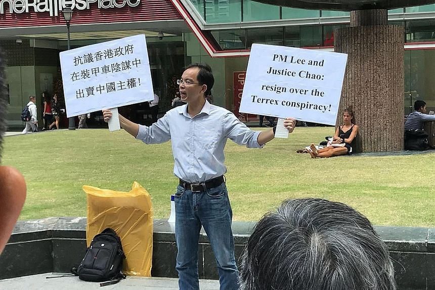Yan Jun was seen holding placards while addressing the lunchtime crowd outside Raffles Place MRT station on Feb 22.