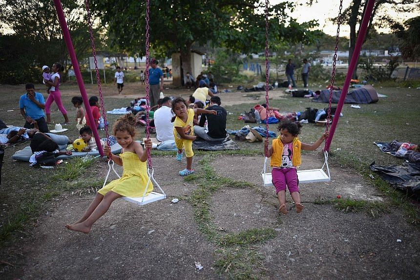 Children, among hundreds of Latin Americans in the migrant caravan that has infuriated US President Donald Trump, play as the group takes a breather in Matias Romero, southern Mexico, on Tuesday.