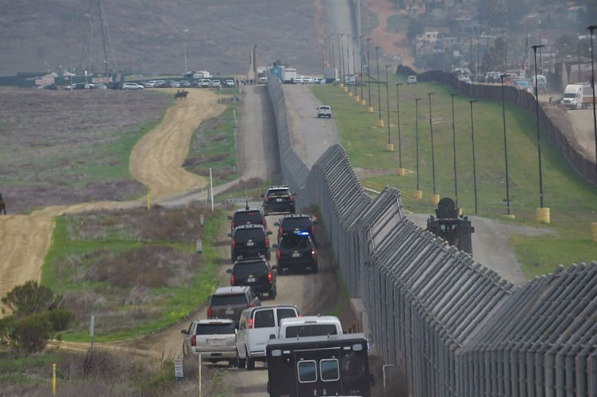 A motorcade carrying US President Donald Trump drives past a US-Mexico border fence as Trump heads for an inspection of border wall prototypes in San Diego, California, on March 13, 2018.