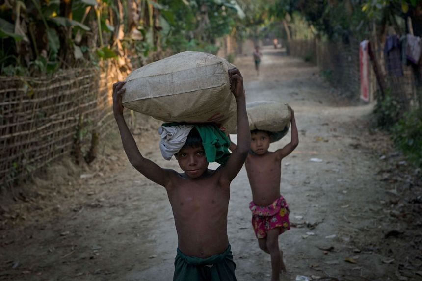 Rohingya children carry sacks at Shan Taung village in the outskirts of Mrauk U township located in Rakhine State close to the Bangladesh border on March 10, 2018.