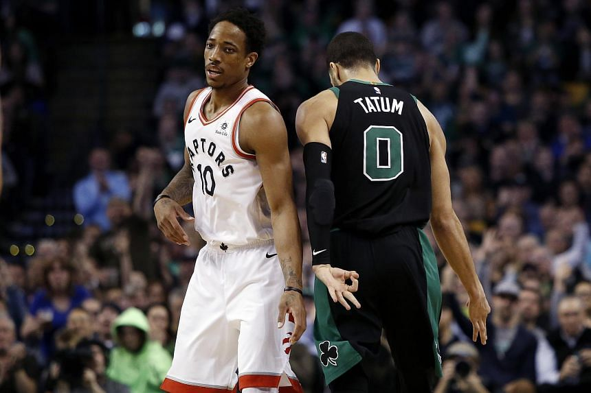 Boston Celtics forward Jayson Tatum signals after making a three point basket as he passes Toronto Raptors guard DeMar DeRozan during the second half of Boston's 110-99 win at TD Garden.