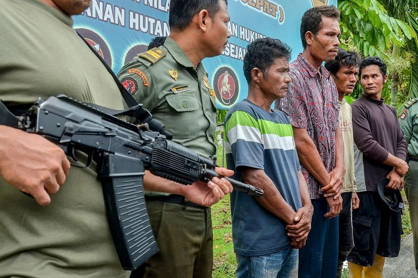 Indonesian armed rangers display the four suspects in the village of Kerta Tunas Jaya.